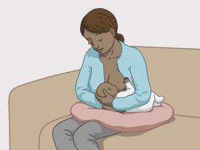 Przykład karmienia piersią nr 2: matka siedzi, natomiast dziecko leży obok niej.