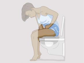 Woman sitting on the toilet and holding an arm between her legs. The focus is on the arm between her legs.